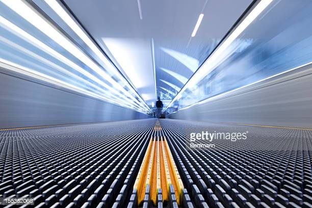 person on a moving escalator with yellow stripes - vanishing point stock pictures, royalty-free photos & images