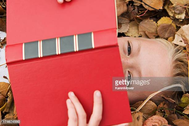 A person on a pile of leaves hiding behind a red book