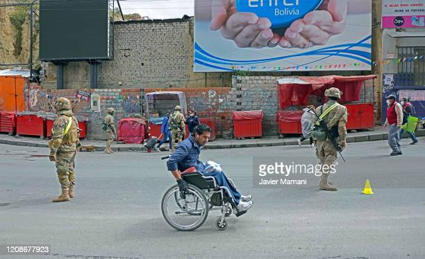 Person on a wheelchair looks on as military officers stand guard at a checkpoint on March 30, 2020 in La Paz, Bolivia. Bolivia has established a...