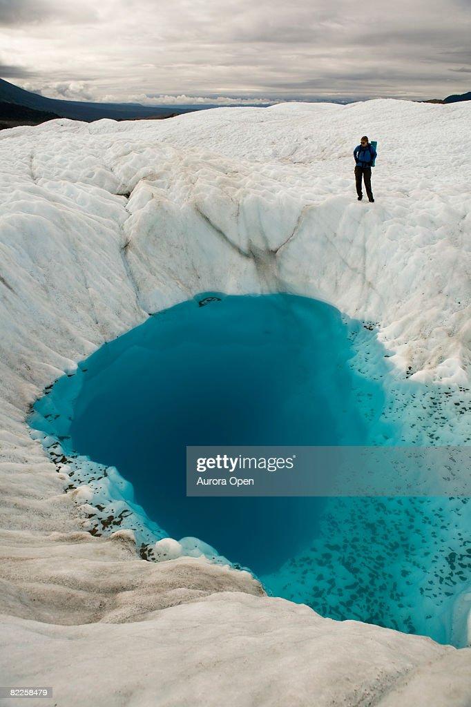 Person on glacier looking at  blue pool, McCarthy, Alaska. : Stock Photo