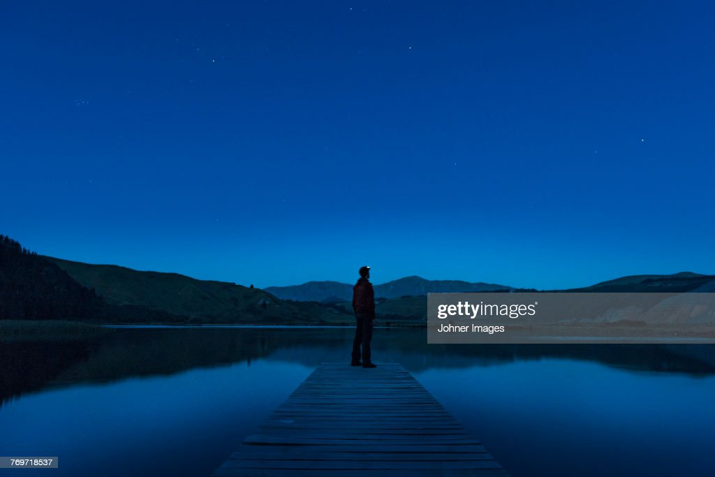 Person on jetty at night : Stock Photo