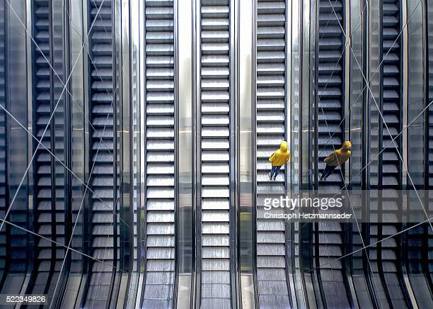 person on moving escalator - symmetry stock photos and pictures