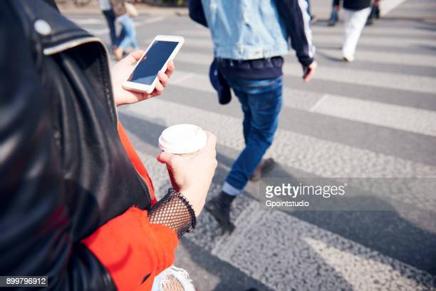Person on pedestrian crossing with coffee and smartphone