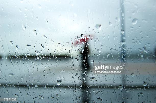 Person on rainy day with red umbrella