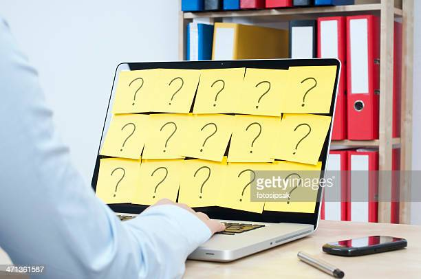 Person on their laptop covered in question marks