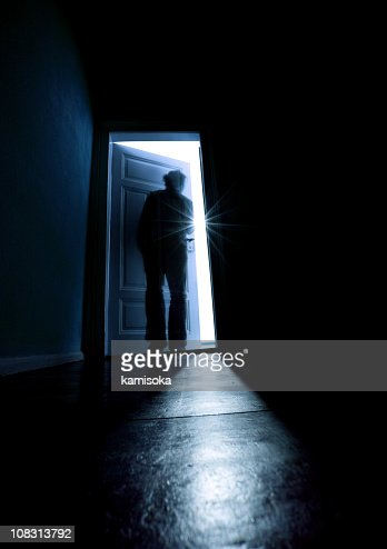 Person Opening A Door From A Dark Room Into The Light
