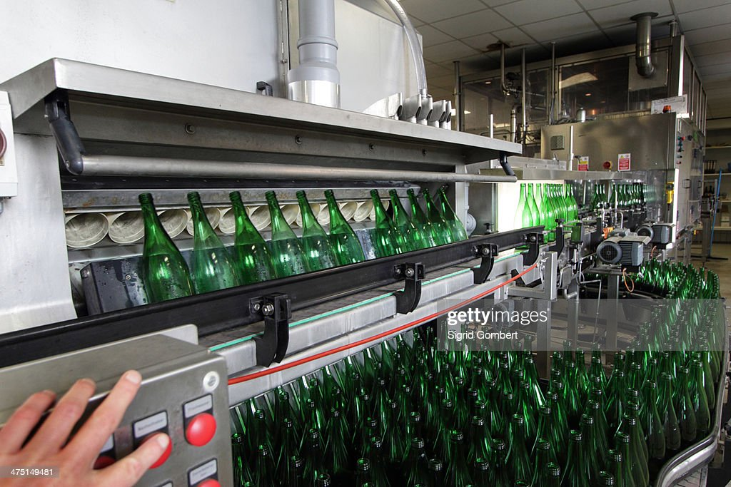 Person operating bottling machine in industrial wine cellar : Stock-Foto