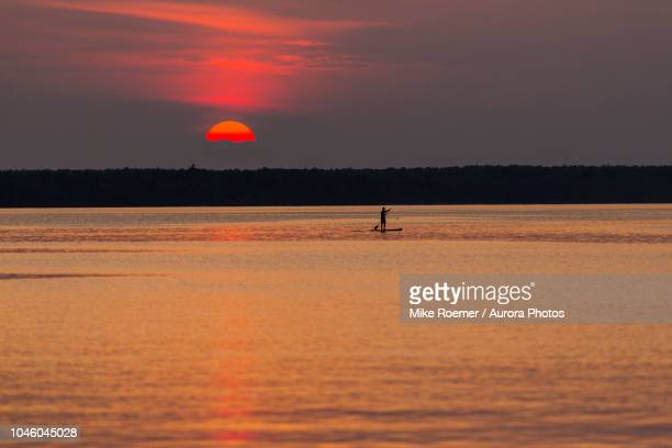 person paddleboarding in lake superior at sunset, munising, michigan, united states - munising michigan stock pictures, royalty-free photos & images