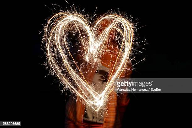 Person Painting Heart With Sparklers At Night