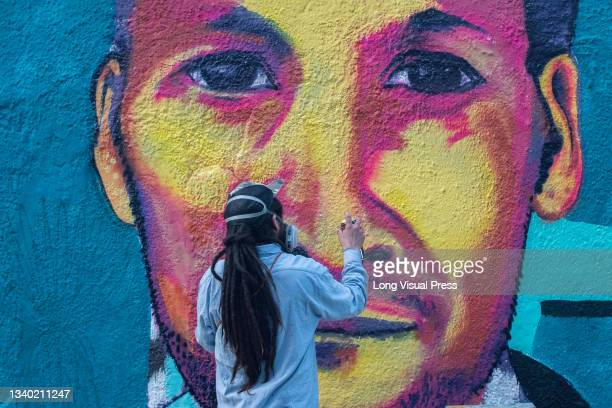 Person paints a mural with the portrait of Javier Ordonez at the Villa Luz CAI police station were police officers tortured Javier Ordonez on...