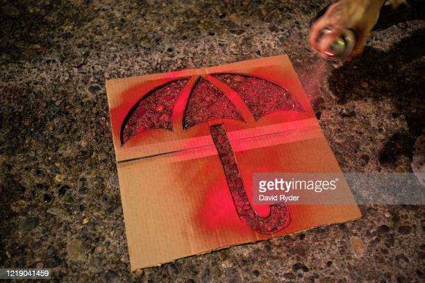 Person paints an umbrella, which has become a common protest image, in a street in front of the Seattle Police Departments East Precinct on June 9,...