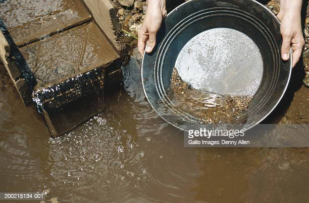 Person panning for gold in river, close-up