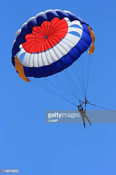 A person parasailing in a big blue sky