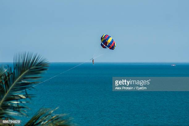 Person Parasailing Over Sea Against Clear Sky