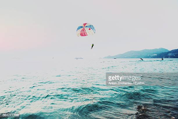 person parasailing over sea against sky - zinchenko stock pictures, royalty-free photos & images