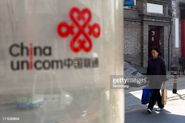 A person passes a China Unicom Ltd phone booth in Beijing China on Tuesday March 29 2011 China Unicom is expected to announce 2010 earnings results...
