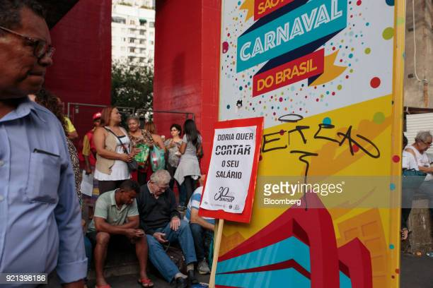A person passes a sign against Joao Doria mayor of Sao Paulo that reads 'Doria Wants To Take Your Salary' during a protest against pension reform in...