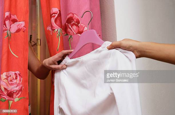 A person passing a shirt to another person in a changing room