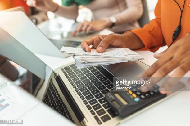 person, die rechnung an computer bezahlt - rechnungswesen stock-fotos und bilder