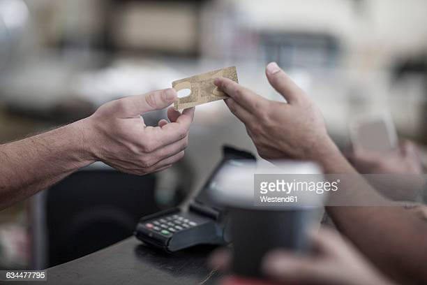 Person paying with credit card at coffee shop