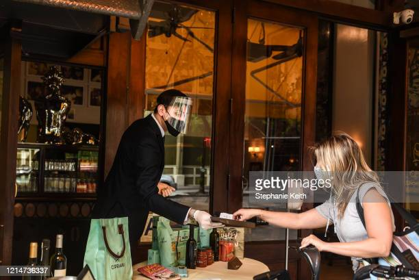Person pays for a to-go order at Cipriano restaurant on May 22, 2020 in the Soho neighborhood in New York City. New York City is currently in its...