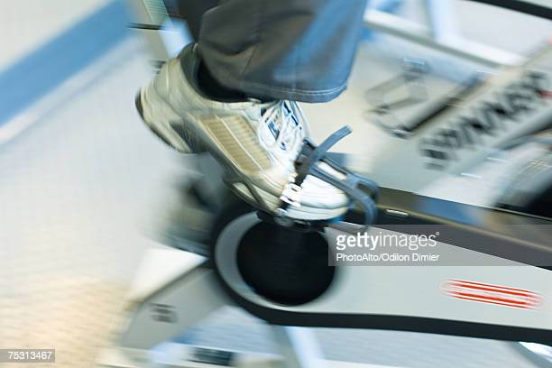Person peddling exercise bike, close-up, blurred motion