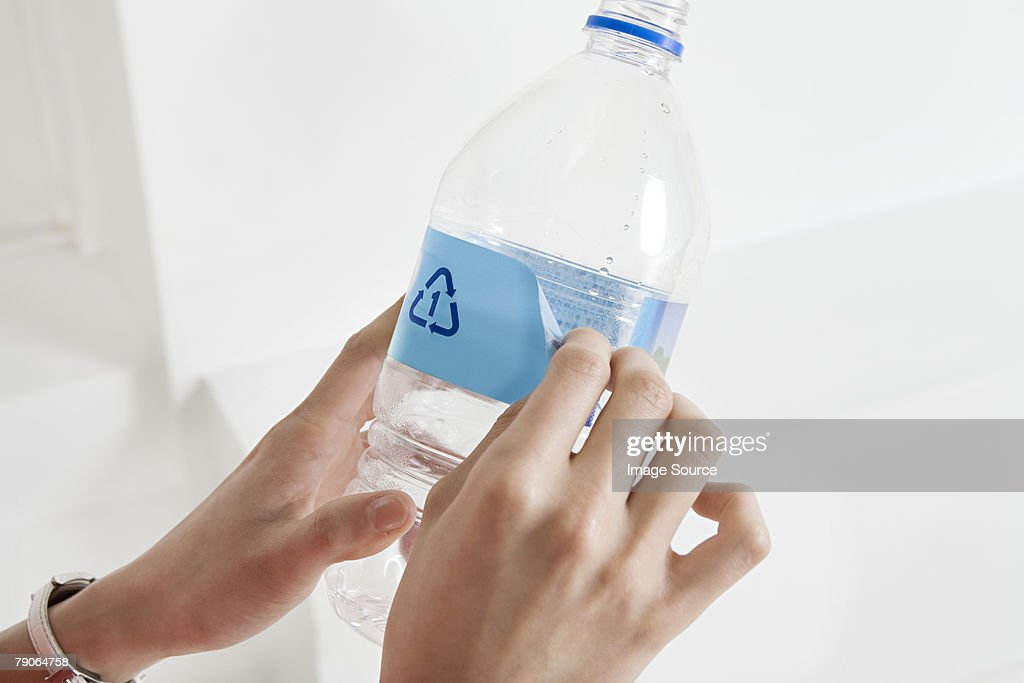 A person peeling off a label off a bottle : Stock Photo