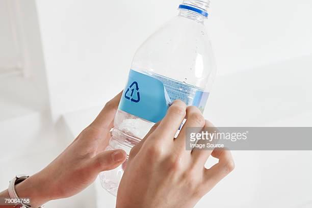 Une personne Peinture écaillée une étiquette sur une bouteille