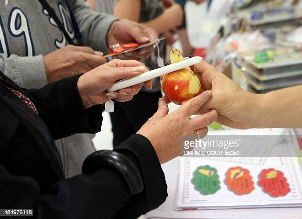 A person peels an apple with a peeler for lefthanded users in the Salle du Pont du Buy in Brivela Gaillarde where writing and cooking workshops were...