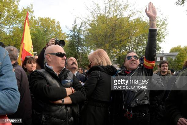 A person performs a fascist salute at the entrance of the Mingorrubio cemetery at El Pardo north of Madrid on October 24 as part of the exhumation of...