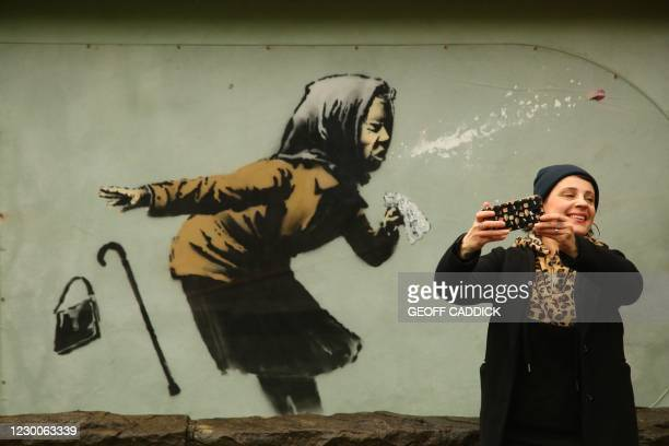 """Person photographs a mural created by British artist Banksy entitled """"Aachoo!!"""" showing a woman wearing a headscarf sneezing and dropping their..."""