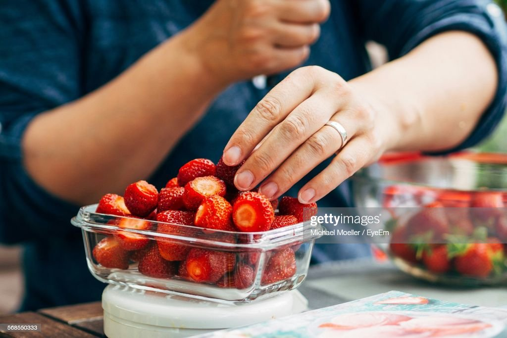 Person Picking Strawberries From Container On Table : Stock Photo
