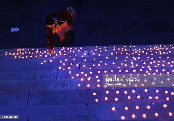 A person places a candle light on the stairs of Brooklyn's Borough Hall during a protest against President Donald Trump's immigration policies on...