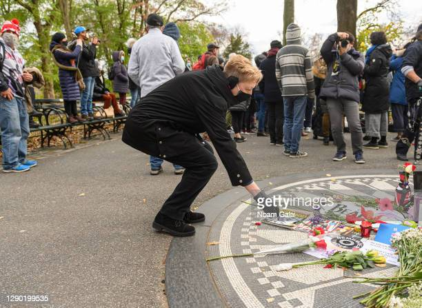 Person places a flower in honor of John Lennon on the 40th anniversary of his death at Strawberry Fields in Central Park on December 08, 2020 in New...