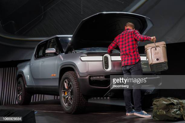Person places items into the front trunk cargo area of the Rivian Automotive Inc R1T electric pickup truck during a demonstration at a reveal event...