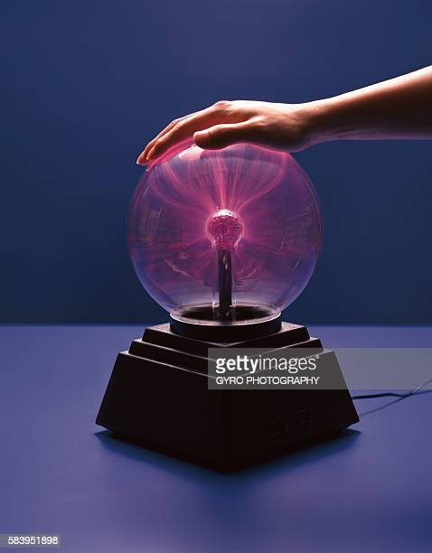 Person placing hand on plasma lamp