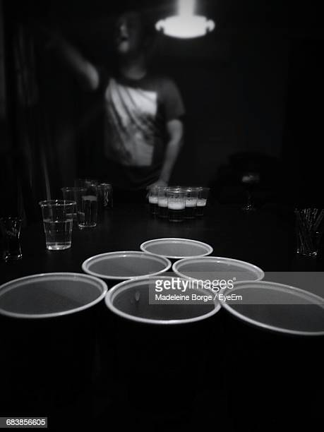 Person Playing Beer Pong In Darkroom