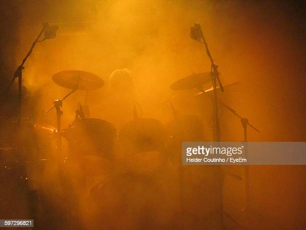 Person Playing Drum In Concert Amidst Smoke