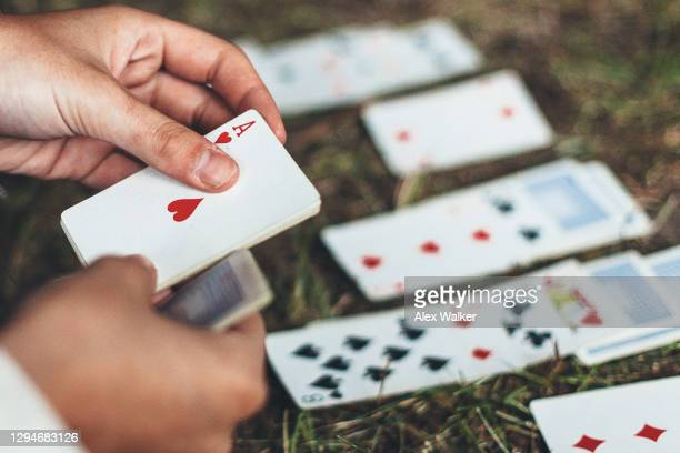 person playing game of cards on ground holding ace - dar cartas imagens e fotografias de stock