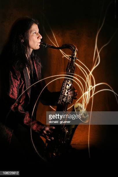 Person Playing Saxophone with Light Streaming From Instrument