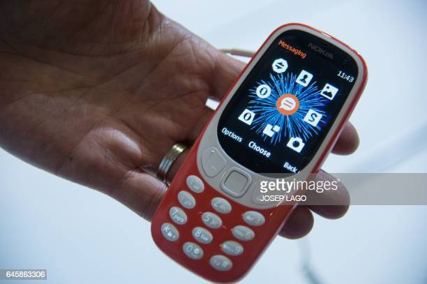 A person plays holds the new 'Nokia 3310' model of Finnish HMD global on the first day of the Mobile World Congress in Barcelonaon on February 27...