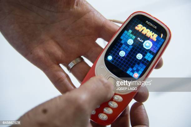 A person plays 'Snake' game on the new 'Nokia 3310' model of Finnish HMD global on the first day of the Mobile World Congress in Barcelonaon on...