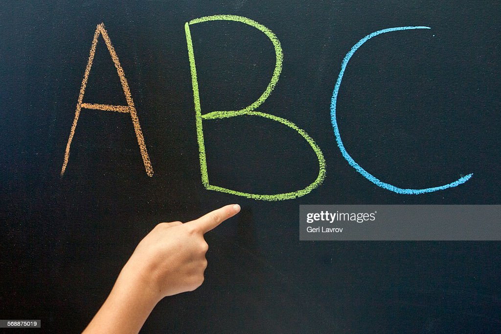 Person pointing to 'ABC' on a blackboard : Stock Photo