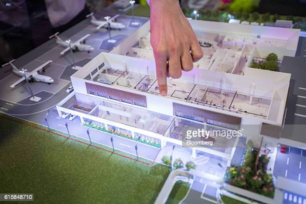 A person points at a model of Seletar Airport's new passenger terminal during a groundbreaking ceremony in Singapore on Thursday Oct 20 2016 The...