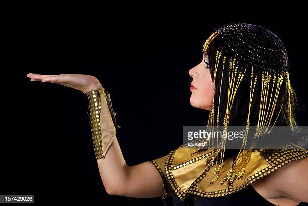 Person portraying Cleopatra on black background