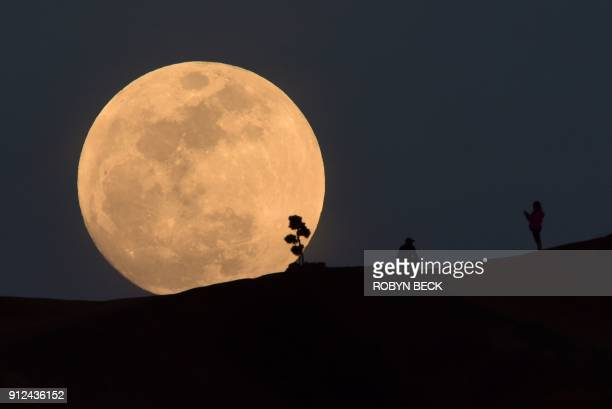 TOPSHOT A person poses for a photo as the moon rises over Griffith Park in Los Angeles California on January 30 2018 Many parts of the globe may...