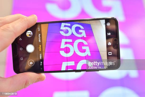A person poses holding a mobile telephone the camera showing a sign advertising 5G mobile telecommunication in a shop in London on January 28 2020...