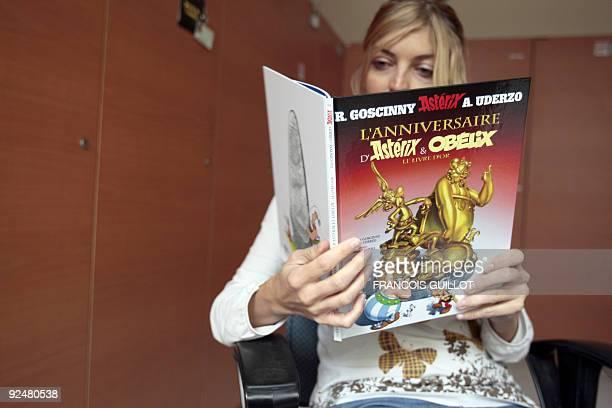 "Person poses reading Asterix last comic book by late writer Rene Goscinny and illustrator Albert Uderzo ""L'anniversaire d'Astérix et Obélix, le livre..."