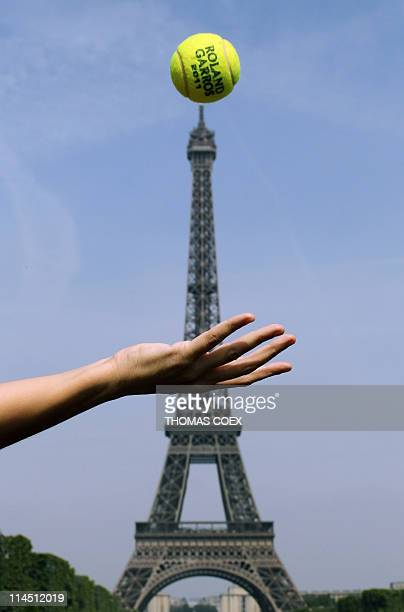 A person poses tossing an official ball of 2011's French Open tennis tournament up in front of the Eiffel Tower on May 20 2011 in Paris The...