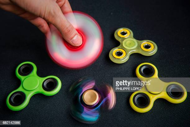 A person poses while holding a 'hand spinner' a new spinningtop toy on May 11 2017 in Paris / AFP PHOTO / PHILIPPE LOPEZ